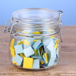 Pieces of paper for lottery in jar on wooden table on blue backg
